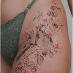 Bird resting on a branch of cherry blossoms - Tattoos for Women