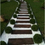 Garden path with wood, white gravel and trimmed boxwood